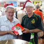 Bar Manager Neil Nicholls with Club Manager Greg Dwiar holding Christmas cake given to the club by Member for Florey Frances Bedford